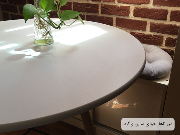 تصويری از سطح ميز ناهار خوری گرد ای 411 به رنگ سفيد که يک عدد گلدان روی ميز قرار داده شده است.