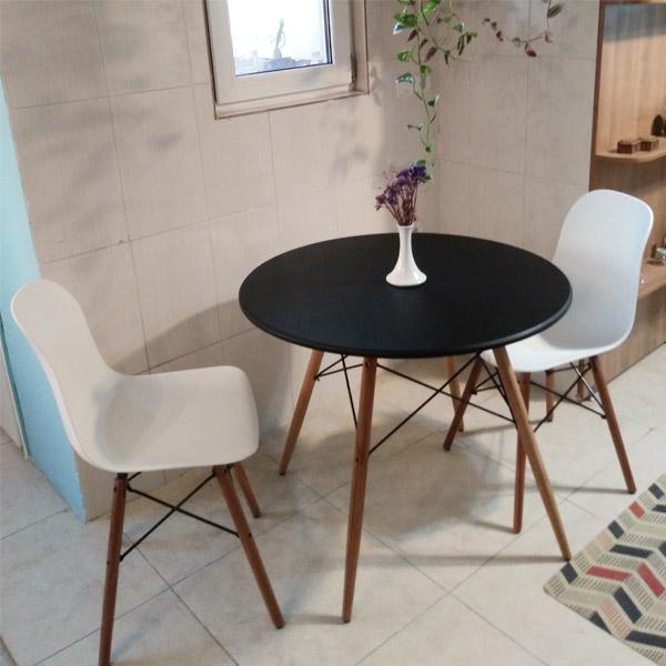 ميز غذا خوری گرد E411 به رنگ مشکی که دو عدد صندلی سفيد رنگ در اطراف آن قرار گرفته اند و يک عدد گلدان سفيد رنگ روی ميز گذاشته شده است.