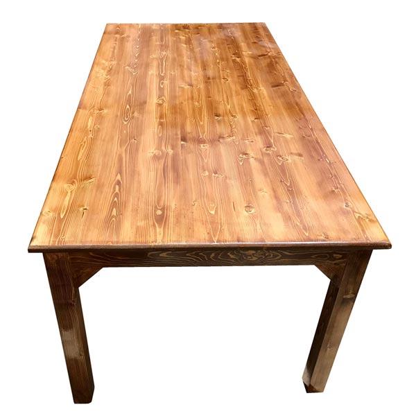 ميز ناهارخوری چوبی به رنگ بژ تيره با سطحی براق از زاويه رو به رو در پس زمينه سفيد