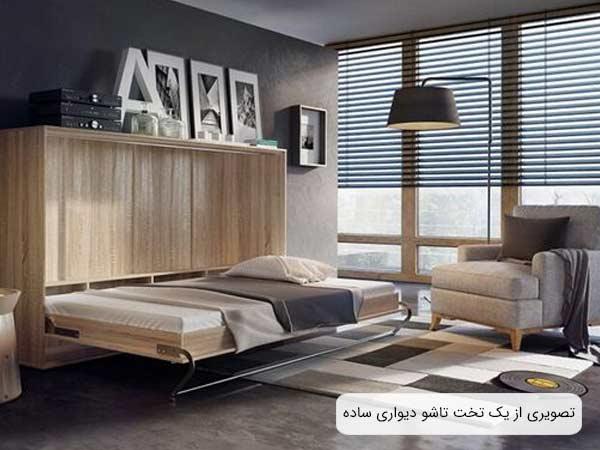 تصويری از يک تخت خواب تاشو ساده با بدنه ای به رنگ بژ روشن و يک عدد تشک و يک پتو که روی آن قرار گرفته اند.
