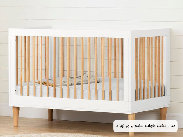 تصوير يک تخت نوزاد به رنگ های کرمی و سفيد در محيطی به همين رنگ.
