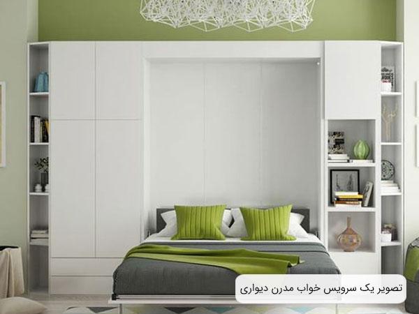 تصويری از يک تخت خواب تاشو با طراحی مدرن با بدنه ای به رنگ سفيد و خوشخواب به رنگ طوسی و سبز روشن .