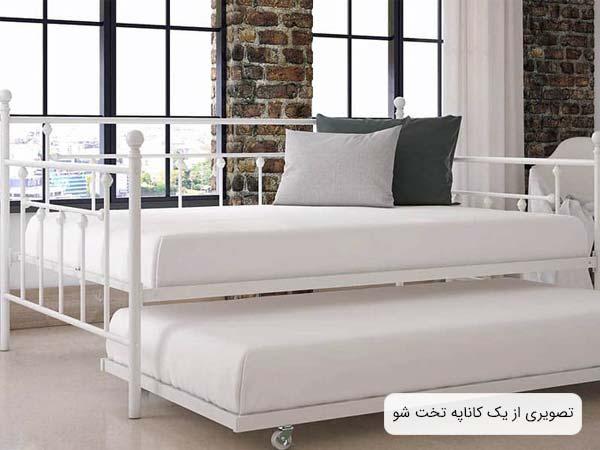 تصويری از يک مبل تختخوابشو مدرن به رنگ سفيد که دو عدد کوسن به رنگ های خاکستری و طوسی روی آن قرار گرفته اند.