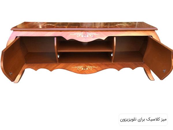 ميز تلويزيون چوبی قهوه ای رنگ با دو در و چند قفسه در پس زمينه سفيد