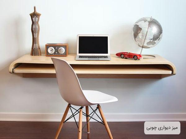 ميز ديواري مناسب اتاق هاي کوچک از جنس چوب و به رنگ کرمي که يک عدد لپ تاپ و چندين وسيله دکوري روي اين ميز قرار گرفته اند