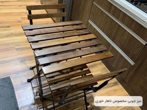 ميز ناهارخوری تاشو مربع شکل به رنگ قهوه ای در کنار دو عدد صندلی ناهار خوری چوبی