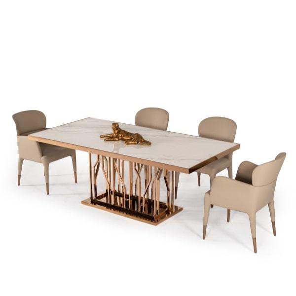تصويری از ميز ناهارخوری استيل شش نفره با پايه های فلزی به رنگ مسی در کنار چهار عدد صندلی ناهارخوری فلزی کرمی رنگ با پس زمينه سفيد .