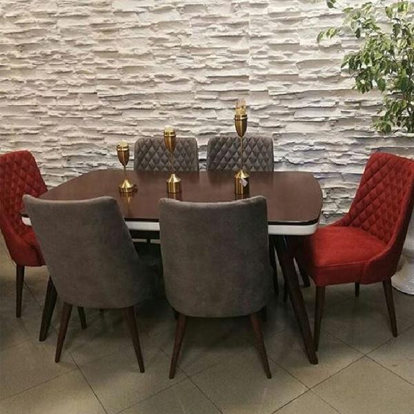 تصويري از ميز ناهار خوری چستر کد 7 با طراحی مدرن که شش عدد صندلی در رنگ های طوسی و قرمز در کنار اين ميز غذا خوري قهوه ای رنگ قرار گرفته اند.