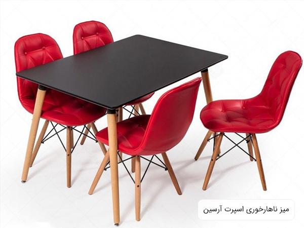 تصويری از ميز ناهار خوری آرسين به رنگ مشکی در کنار چهار عدد صندلی به رنگ قرمز با پس زمينه سفيد .