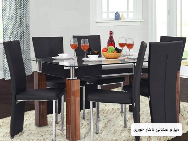 تصويری از ميز ناهار خوری شیشه ای روساریو به همراه شيش عدد صندلی ناهار خوری مشکی رنگ با روکش چرمی و خوراکی ها و غذا هايی که روی ميز قرار گرفته اند.