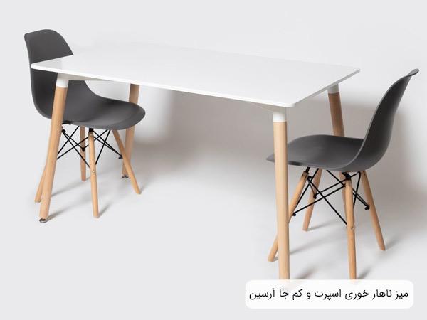 تصويری از ميز ناهار خوری آرسين با سطح سفيد رنگ در کنار دو عدد صندلی ناهار خوری مشکی در پس زمينه سفيد.