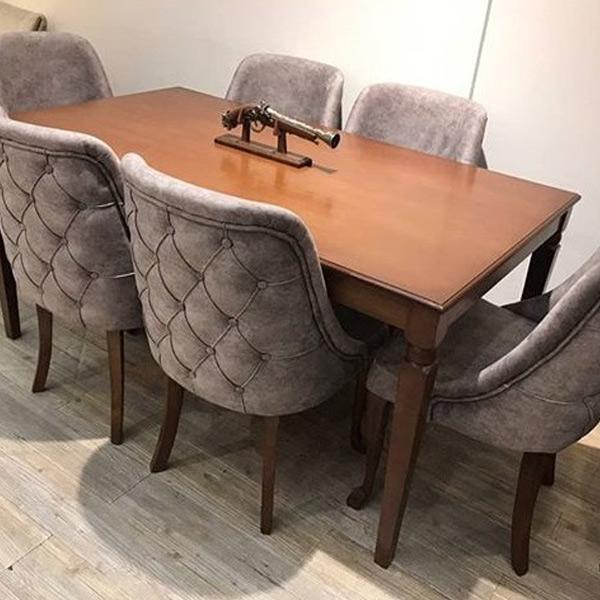 تصويری از ميز ناهار خوری چستر شش نفره که روکش صندلی ها به رنگ خاکستری می باشد و خود ميز به رنگ قهوه ای روشن و بر روی ميز يک اسلحه تزئينی قرار داده شده است.