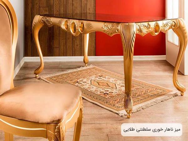ميز ناهار خوری لوکس طرح سلطنتی به رنگ طلايی با صحفحه شيشه ای که يک عدد صندلی ناهار خوری همين مدلی در کنار آن قرار گرفته است و يک فرش زير ميز انداخته شده است.