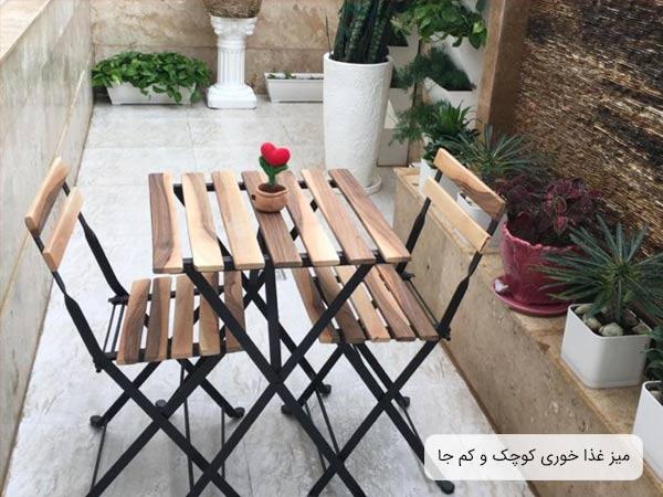 ميز و صندلی ناهار خوری چوبی به رنگ کرمی روشن در ابعاد کوچک که در کنار چند گلدان قرار گرفته است