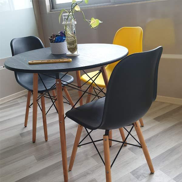 ميز و صندلی ناهار خوری گرد به رنگ مشکی و يک عدد صندلی زرد رنگ که در کنار این میز قرار گرفته است.