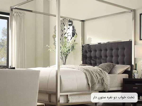 تصويری از يک تخت دو نفره سايه بانی با بدنه ای به رنگ سفيد و ستون های نقره ای رنگ و تاجی به رنگ طوسی.