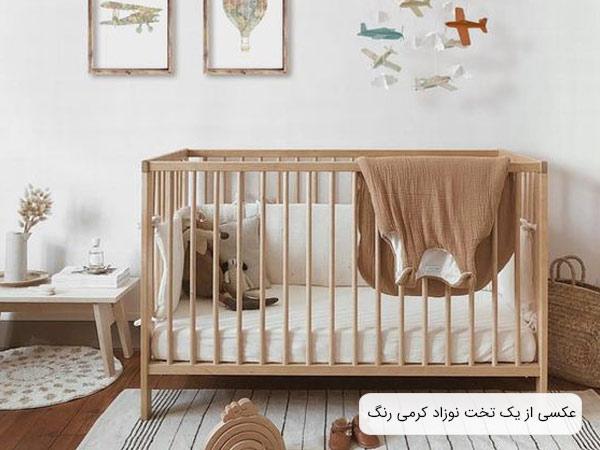 عکسی از يک تخت خواب نوزاد کرمی رنگ در کنار اشيا و لوازمی با همين طيف رنگ و در يک اتاق با ديوار سفيد .