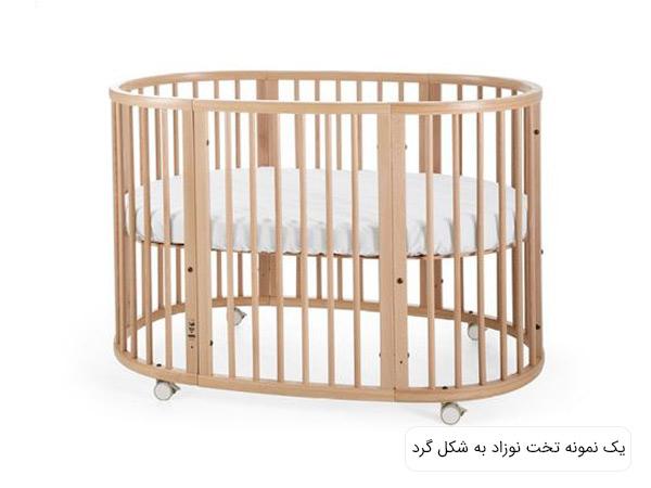 تصويری از يک تخت نوزاد به شکل گرد با بدنه کرمی رنگ و تشک سفيد و چرخ دار در پس زمينه سفيد.