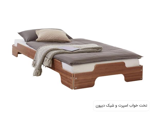 تخت خواب ديپون با بدنه ای به رنگ قهوه ای روشن ، تشک سفيد و پتو و بالشت طوسی رنگ در پس زمينه سفيد.