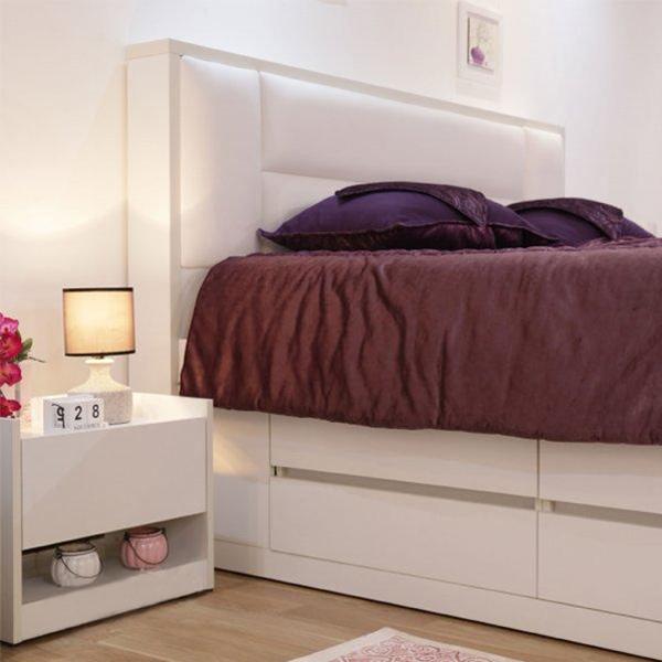 تصويری از سرويس خواب مدرن رومنس که شامل يک تخت خواب کشو دار و يک پاتختی می باشد. روي پاتختی سفيد رنگ يک عدد آباژور و چند وسيله دکوری قرار داده شده است.