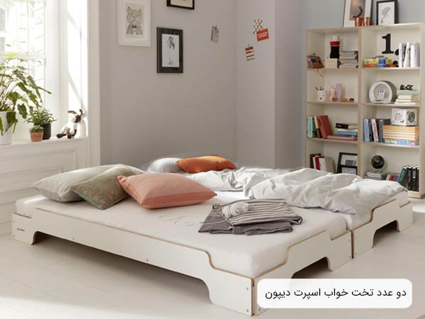 تصويري از دو عدد تخت خواب ديپون a26 به رنگ سفيد در کنار هم که در مرکر يک اتاق قرار گرفته اند.